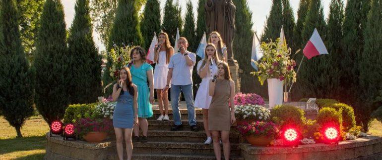 na schodach przed pomnikiem stoji 6 diewczyn i jeden męzczyzna trzymją w rękach mikrofony