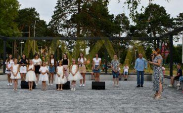 grupa osób stoi w amfiteatrze w koło publicznośc