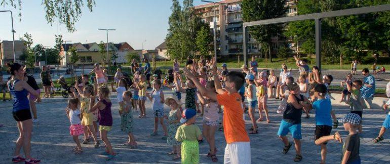 Grupka dzieci stoi na świeżym powietrzu i naśladują ruchy Pani która stoi przed nimi